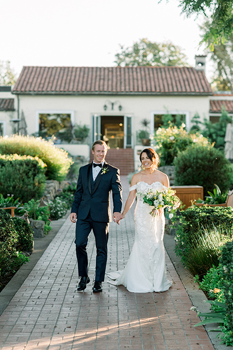 Inn-at-Rancho-Santa-Fe-wedding-bride-and-groom-holing-hands-in-front-of-white-building-bride-in-a-formfitting-lace-gown-with-off-the-shoulder-sleeve-detailing-and-the-groom-in-a-navy-blue-tuxedo-with-a-shawl-lapel-and-black-bow-tie