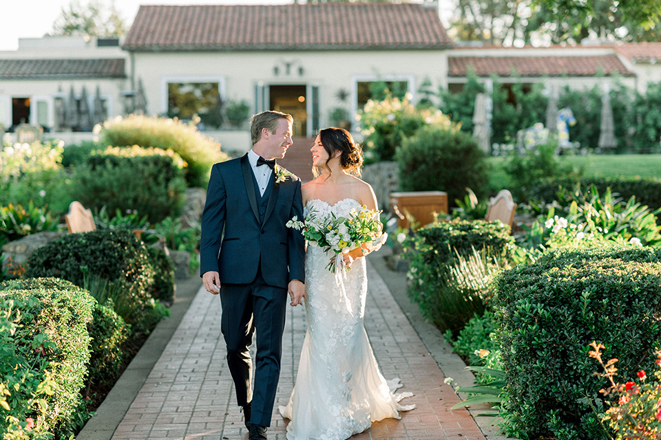 Inn-at-Rancho-Santa-Fe-wedding-bride-and-groom-walking-in-front-of-white-building-bride-in-a-formfitting-lace-gown-with-off-the-shoulder-sleeve-detailing-and-the-groom-in-a-navy-blue-tuxedo-with-a-shawl-lapel-and-black-bow-tie