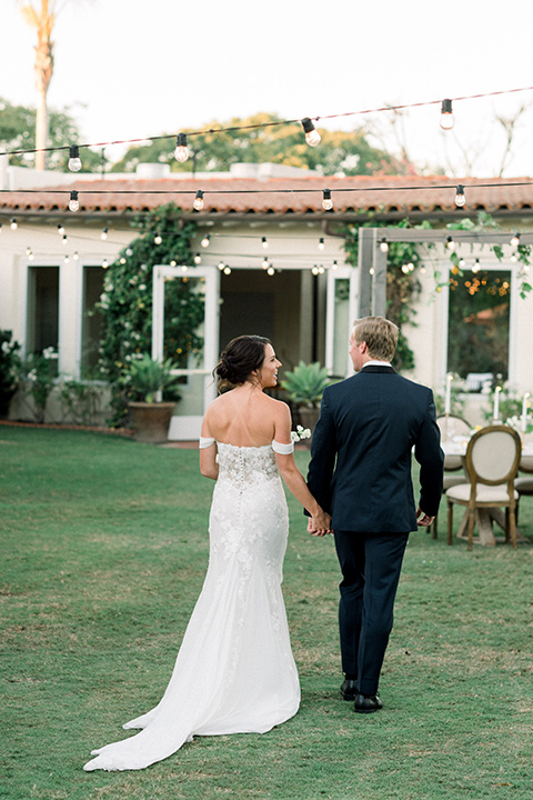 Inn-at-Rancho-Santa-Fe-wedding-bride-and-groom-walking-towards-reception-bride-in-a-formfitting-lace-gown-with-off-the-shoulder-sleeve-detailing-and-the-groom-in-a-navy-blue-tuxedo-with-a-shawl-lapel-and-black-bow-tie
