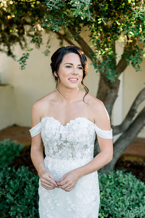 Inn-at-Rancho-Santa-Fe-wedding-bride-standing-holding-flowers-in-a-formfitting-lace-gown-with-off-the-shoulder-sleeve-detailing