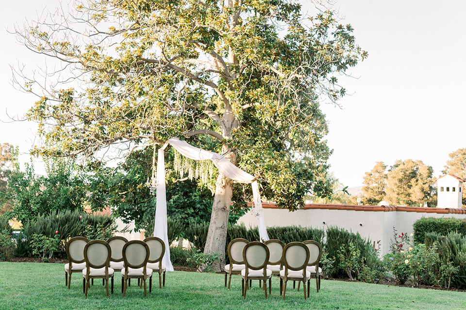 Inn-at-Rancho-Santa-Fe-wedding-ceremony-set-up-with-wooden-chairs-and-white-flowing-material-hanging-from-the-trees-as-the-wedding-arch