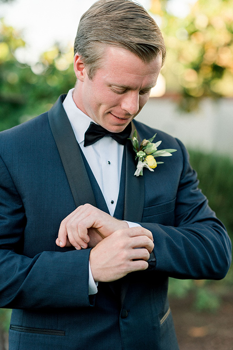 Inn-at-Rancho-Santa-Fe-wedding-groom-fixing-sleeve-in-a-navy-blue-tuxedo-with-a-shawl-lapel-and-black-bow-tie