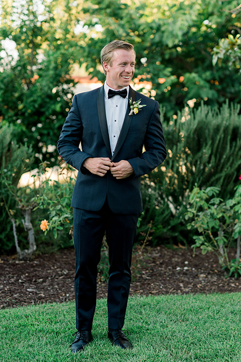 Inn-at-Rancho-Santa-Fe-wedding-groom-standing-in-a-navy-blue-tuxedo-with-a-shawl-lapel-and-black-bow-tie