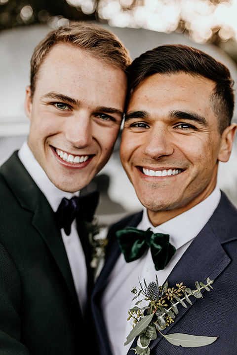 retro-ranch-styled-shoot-close-up-on-grooms-one-groom-wearing-a-dark-blue-suit-with-a-green-velvet-bow-tie-and-the-other-wearing-a-green-suit-with-a-blue-velvet-bow-tie