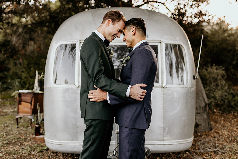 retro-ranch-styled-shoot-couple-in-front-of-airstream-one-groom-wearing-a-dark-blue-suit-with-a-green-velvet-bow-tie-the-other-groom-wearing-a-green-suit-with-a-blue-velvet-bow-tie