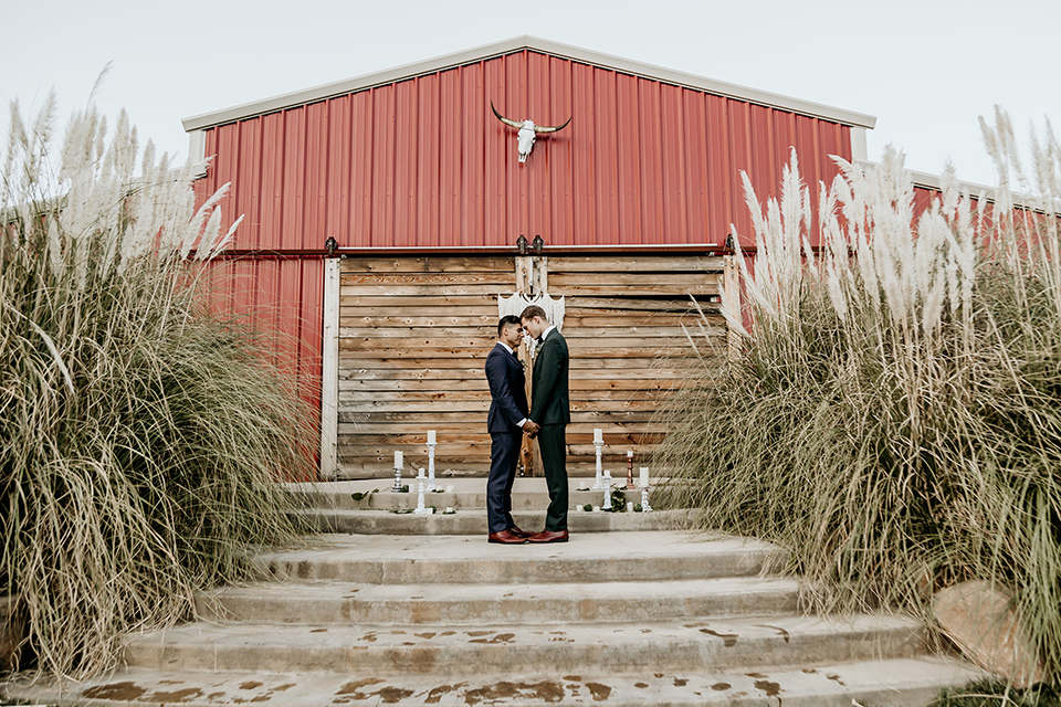 retro-ranch-styled-shoot-grooms-at-ceremony-space-one-groom-wearing-a-dark-blue-suit-with-a-green-velvet-bow-tie-the-other-groom-wearing-a-green-suit-with-a-blue-velvet-bow-tie