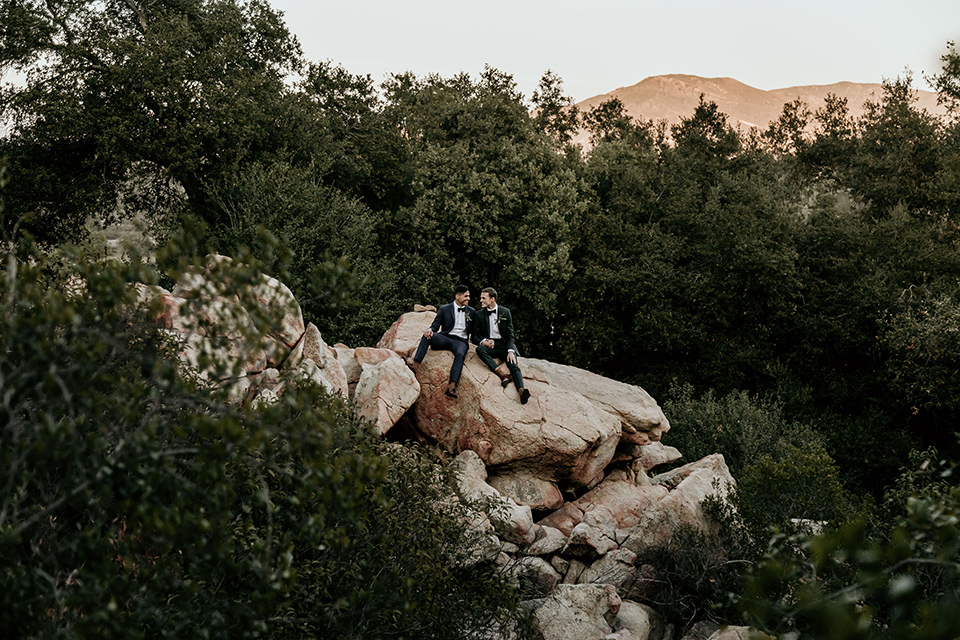 retro-ranch-styled-shoot-grooms-on-rock-one-groom-wearing-a-dark-blue-suit-with-a-green-velvet-bow-tie-the-other-groom-wearing-a-green-suit-with-a-blue-velvet-bow-tie