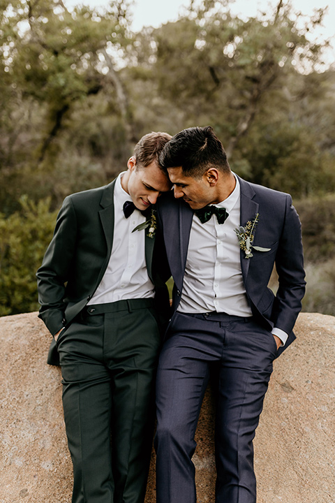 retro-ranch-styled-shoot-grooms-resting-on-rock-together-one-groom-wearing-a-dark-blue-suit-with-a-green-velvet-bow-tie-and-the-other-wearing-a-green-suit-with-a-blue-velvet-bow-tie