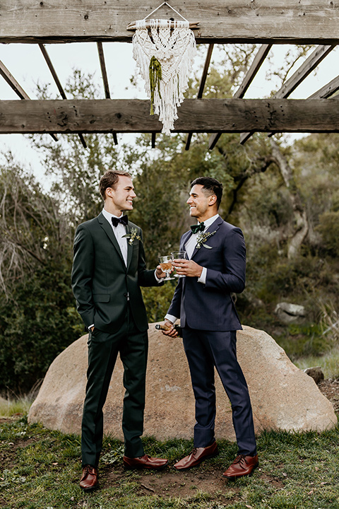 retro-ranch-styled-shoot-grooms-under-macrame-one-groom-wearing-a-dark-blue-suit-with-a-green-velvet-bow-tie-and-the-other-wearing-a-green-suit-with-a-blue-velvet-bow-tie