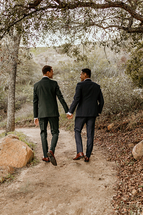 retro-ranch-styled-shoot-grooms-walking-away-one-groom-wearing-a-dark-blue-suit-with-a-green-velvet-bow-tie-and-the-other-wearing-a-green-suit-with-a-blue-velvet-bow-tie