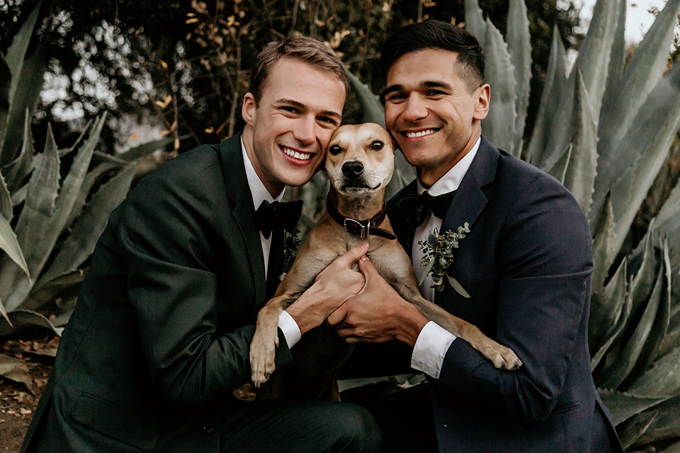 retro-ranch-styled-shoot-grooms-with-dog-one-groom-wearing-a-dark-blue-suit-with-a-green-velvet-bow-tie-the-other-groom-wearing-a-green-suit-with-a-blue-velvet-bow-tie