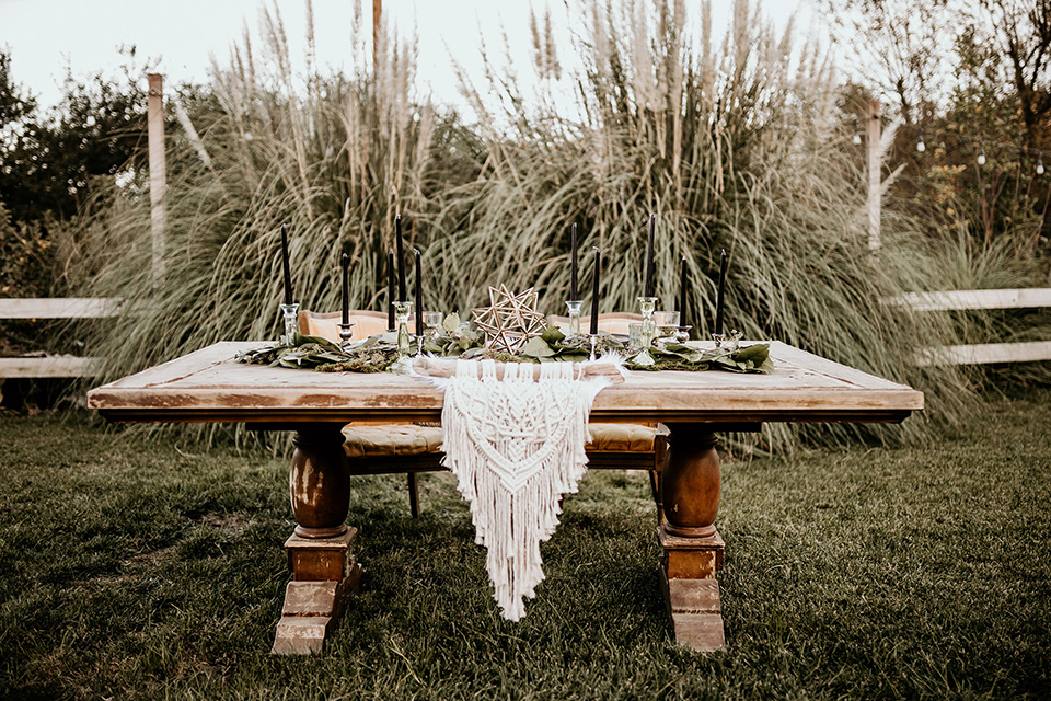 retro-ranch-styled-shoot-table-set-up-with-a-wooden-table-and-bohemian-inspired-plates-and-goldware