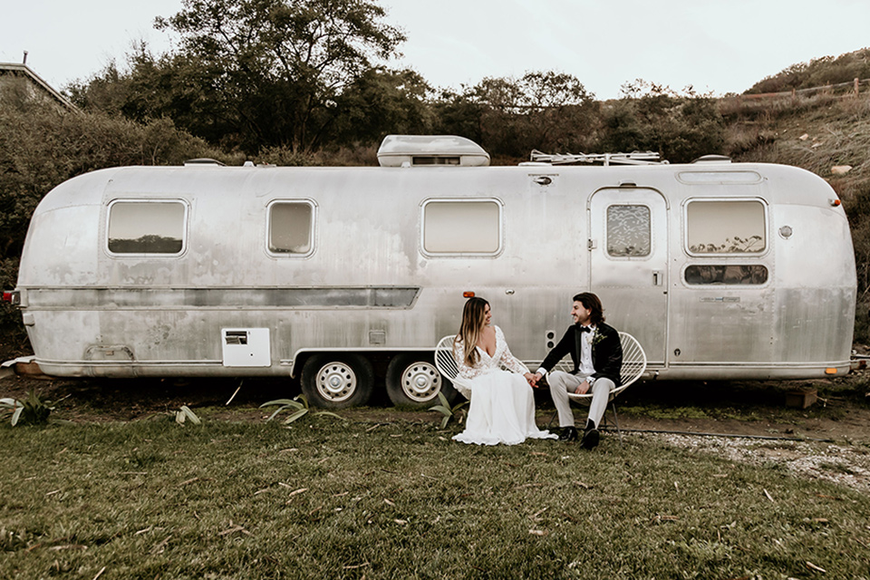 The-Retro-Ranch-Shoot-bride-and-groom-in-front-of-trailer-bride-in-a-boho-gown-with-long-lace-sleeves-and-groom-in-a-velvet-tuxedo-jacket-in-black-with-light-grey-pants