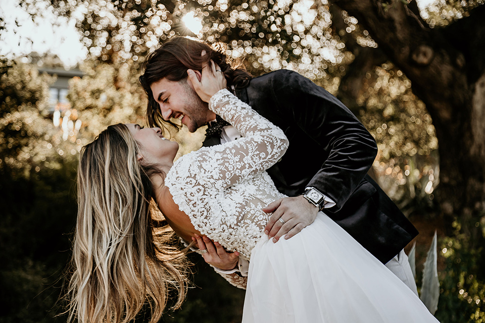 The-Retro-Ranch-Shoot-groom-dipping-bride-boho-gown-with-long-lace-sleeves-and-groom-in-a-velvet-tuxedo-jacket-in-black-with-light-grey-pants