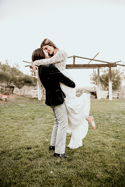 The-Retro-Ranch-Shoot-groom-holding-bride-bride-wearing-a-flowing-gown-with-lace-long-sleeves-groom-in-a-black-velvet-coat-with-light-grey-pants