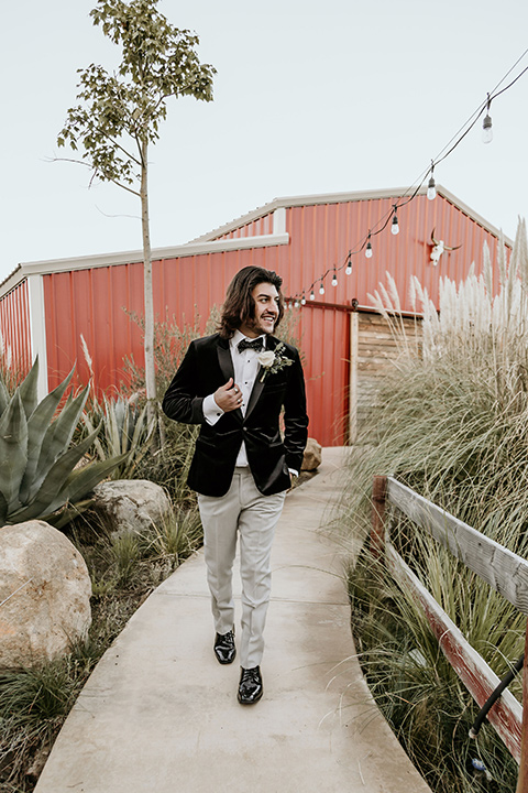 The-Retro-Ranch-Shoot-groom-walking-in-a-black-velvet-coat-with-grey-pants