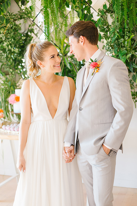 The-Ruby-Street-70s-Inspired-Shoot-bride-and-groom-looking-at-each-other-bride-in-a-white-ballgown-with-a-plunging-neck-line-and-hair-up-in-a-ponytail-groom-in-a-light-grey-suit-with-a-champagne-long-tie