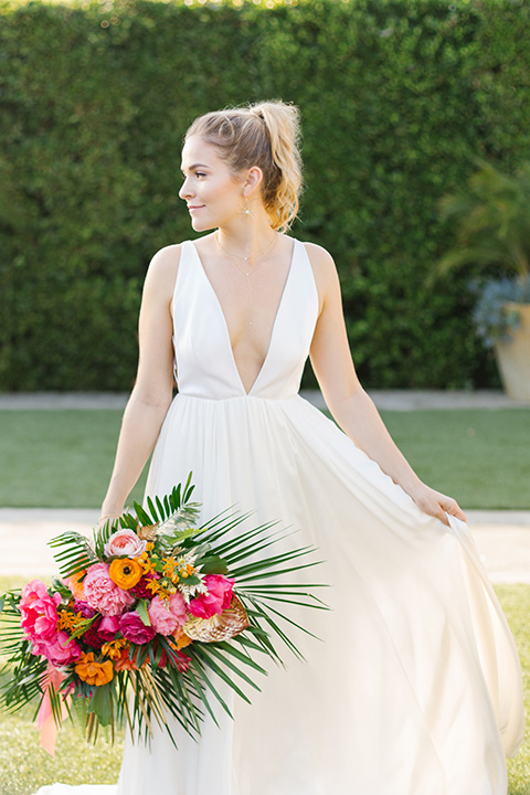 The-Ruby-Street-70s-Inspired-Shoot-bride-looking-to-the-side-in-a-white-ballgown-with-a-plunging-neck-line-and-hair-up-in-a-ponytail