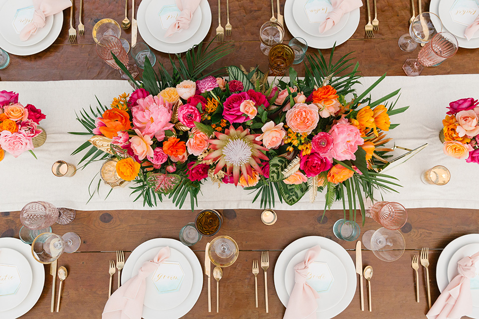 The-Ruby-Street-70s-Inspired-Shoot-table-decor-overhead-with-white-linens-and-white-plate-and-bright-table-florals