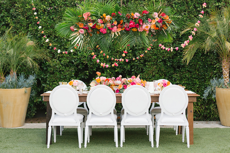 The-Ruby-Street-70s-Inspired-Shoot-table-setup-with-white-linens-and-white-plate-and-bright-table-florals