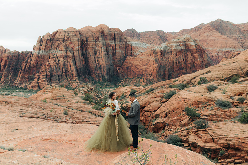 Utah-anow-canyon-shoot-bride-and-groom-facing-each-other-with-vow-book-the-bride-wears-an-olive-green-tulle-skirt-with-an-ivory-lace-long-sleeved-top-and-the-groom-in-a-café-brown-coat-with-a-dark-blue-pant-and-vest-with-a-gold-velvet-bow-tie
