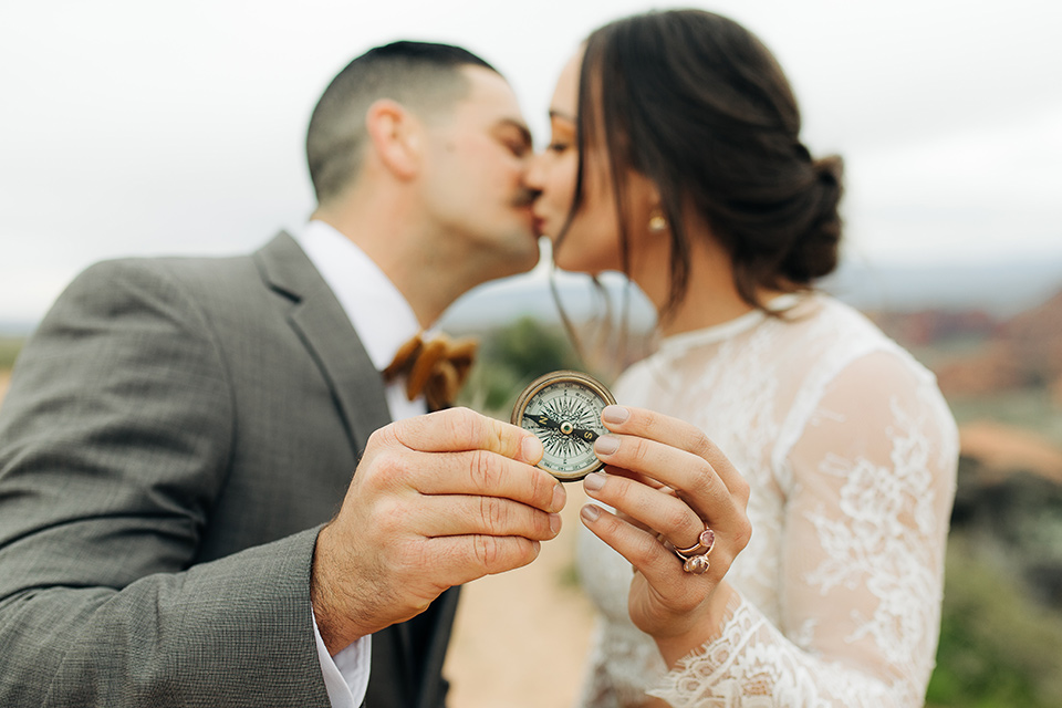 Utah-anow-canyon-shoot-bride-and-groom-holding-compass-the-bride-wears-an-olive-green-tulle-skirt-with-an-ivory-lace-long-sleeved-top-and-the-groom-in-a-café-brown-coat-with-a-dark-blue-pant-and-vest-with-a-gold-velvet-bow-tie