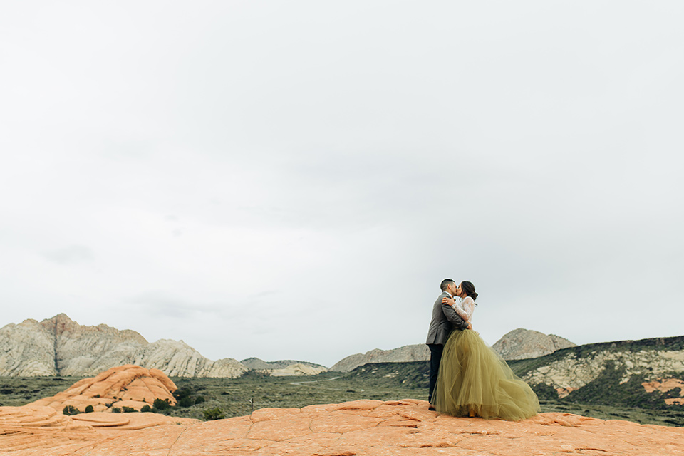Utah-anow-canyon-shoot-bride-and-groom-holding-eachother-the-bride-wears-an-olive-green-tulle-skirt-with-an-ivory-lace-long-sleeved-top-and-the-groom-in-a-café-brown-coat-with-a-dark-blue-pant-and-vest-with-a-gold-velvet-bow-tie
