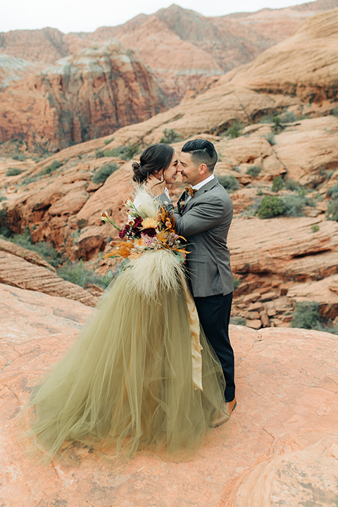 Utah-snow-canyon-shoot-bride-and-groom-laughing-and-touching-heads-the-bride-is-wearing-an-olive-green-tulle-skirt-and-an-ivory-lace-crop-top-with-long-sleeves-the-groom-in-a-café-brown-suit-with-blue-navy-pants-and-vest-with-a-gold-velvet-bow-tie