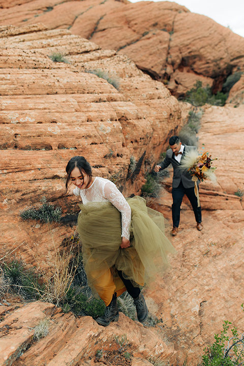 Utah-snow-canyon-shoot-bride-and-groom-with-boots-hiking-the-bride-is-wearing-an-olive-green-tulle-skirt-and-an-ivory-lace-crop-top-with-long-sleeves-the-groom-in-a-café-brown-suit-with-blue-navy-pants-and-vest-with-a-gold-velvet-bow-tie