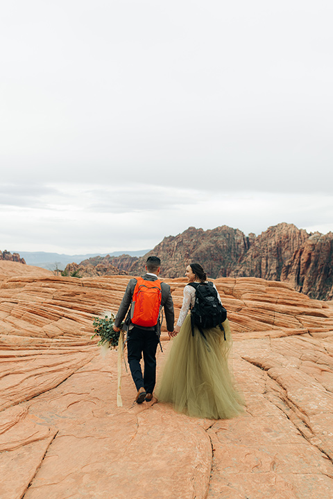 Utah-snow-canyon-shoot-bride-and-groom-with-hiking-packs-walking-away-the-bride-is-wearing-an-olive-green-tulle-skirt-and-an-ivory-lace-crop-top-with-long-sleeves-the-groom-in-a-café-brown-suit-with-blue-navy-pants-and-vest-with-a-gold-velvet-bow-tie