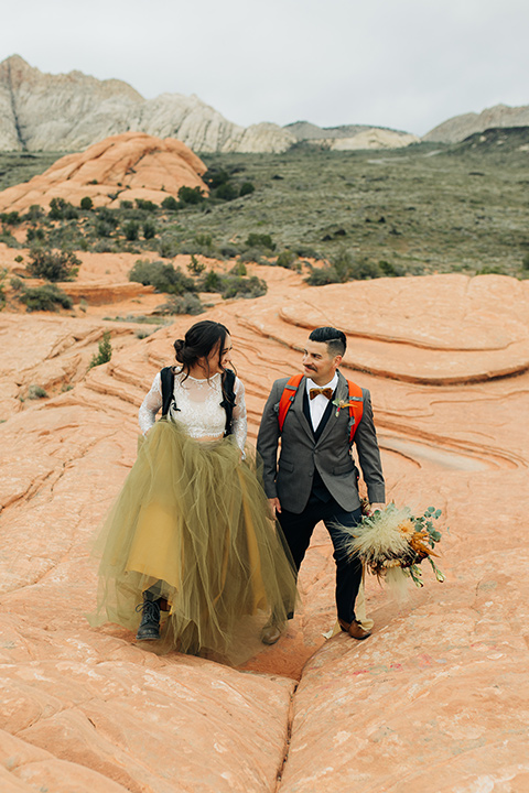Utah-snow-canyon-shoot-bride-and-groom-with-hiking-packs-walking-towards-camera-bride-wearing-a-olive-green-tulle-skirt-with-an-ivory-lace-long-sleeve-crop-top-and-the-groom-is-in-a-café-brown-coat-with-a-blue-pair-of-pants-and-a-vest-with-a-gold-velvet-bow-tie