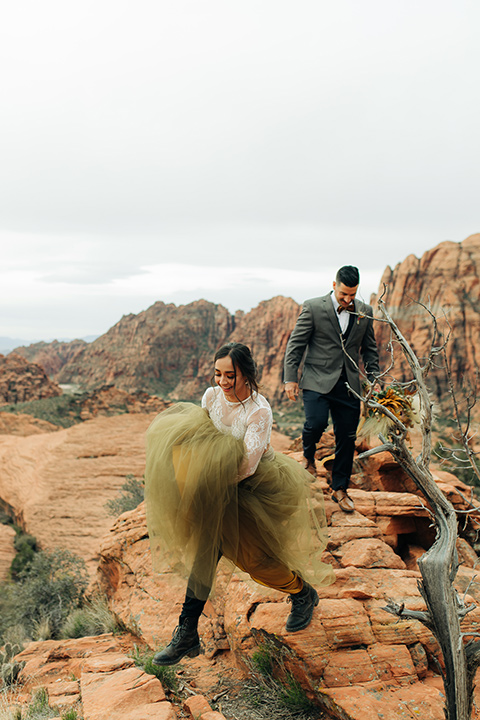 Utah-snow-canyon-shoot-bride-jumping-from-rock-to-rock-bride-wearing-a-olive-green-tulle-skirt-with-an-ivory-lace-long-sleeve-crop-top-and-the-groom-is-in-a-café-brown-coat-with-a-blue-pair-of-pants-and-a-vest-with-a-gold-velvet-bow-tie