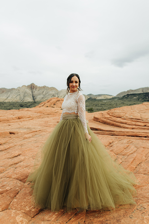 Utah-snow-canyon-shoot-bride-looking-over-her-shoulder-wearing-an-olive-green-tulle-skirt-and-an-ivory-lace-crop-top-with-long-sleeves