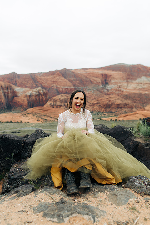 Utah-snow-canyon-shoot-bride-with-hiking-boots-wearing-an-olive-green-tulle-skirt-and-an-ivory-lace-crop-top-with-long-sleeves
