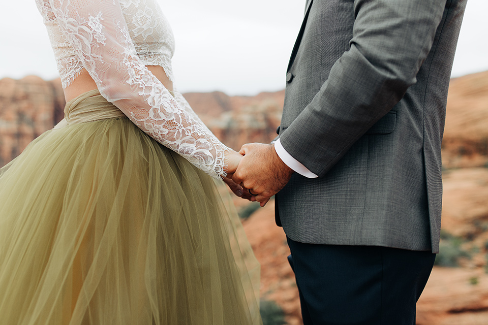 Utah-anow-canyon-shoot-close-up-of-bride-and-groom-holding-hands-the-bride-wears-an-olive-green-tulle-skirt-with-an-ivory-lace-long-sleeved-top-and-the-groom-in-a-café-brown-coat-with-a-dark-blue-pant-and-vest-with-a-gold-velvet-bow-tie