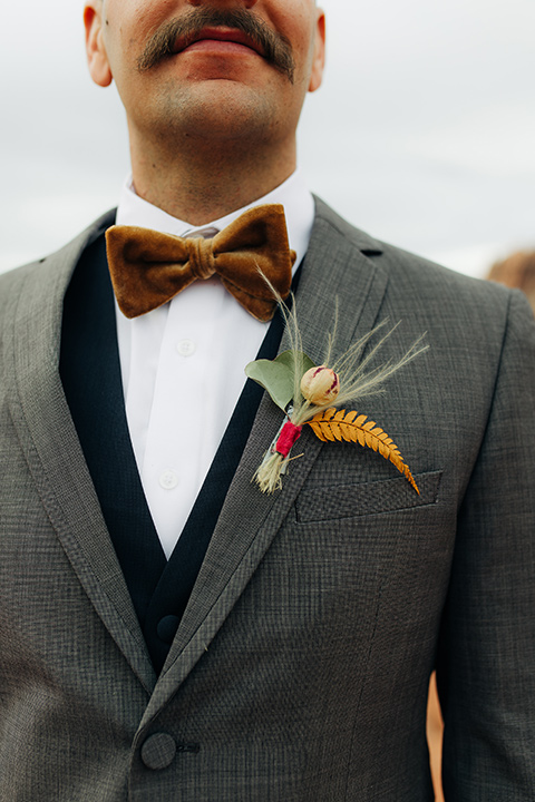 Utah-snow-canyon-shoot-groom-attire-close-up-in-a-café-brown-suit-with-blue-navy-pants-and-vest-with-a-gold-velvet-bow-tie
