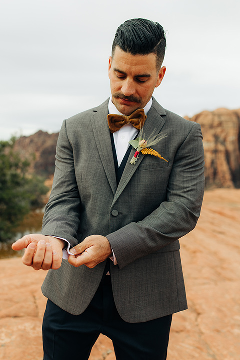 Utah-snow-canyon-shoot-groom-fixing-cuff-in-a-café-brown-coat-with-a-blue-pair-of-pants-and-a-vest-with-a-gold-velvet-bow-tie