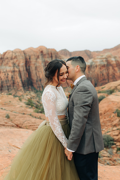 Utah-snow-canyon-shoot-groom-whispering-in-brides-ear-bride-wearing-a-olive-green-tulle-skirt-with-an-ivory-lace-long-sleeve-crop-top-and-the-groom-is-in-a-café-brown-coat-with-a-blue-pair-of-pants-and-a-vest-with-a-gold-velvet-bow-tie