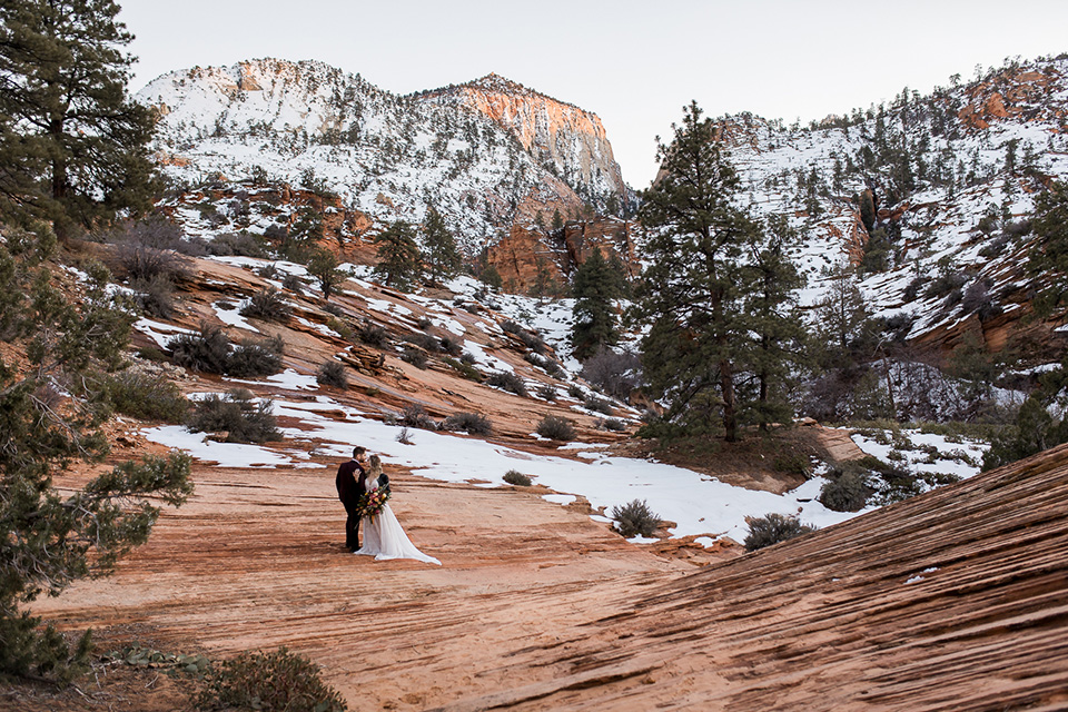 Utah-Shoot-bride-and-groom-far-away-shot-on-cliff-bride-in-a-flowing-tulle-gown-and-lace-bodice-with-a-leather-jacket-while-the-groom-is-in-a-burgundy-tuxedo-with-a-long-black-tie
