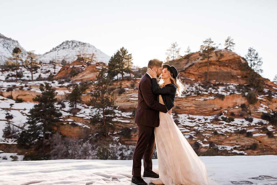 Utah-Shoot-bride-and-groom-kissing-bride-in-a-flowing-tulle-gown-and-lace-bodice-with-a-leather-jacket-while-the-groom-is-in-a-burgundy-tuxedo-with-a-long-black-tie