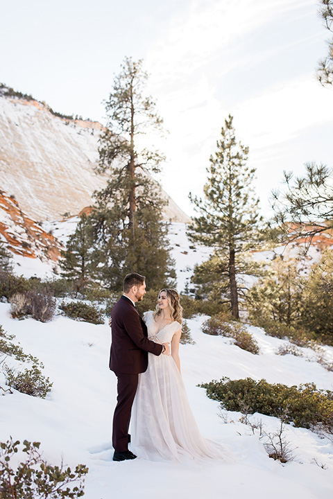 Utah-Shoot-bride-and-groom-looking-at-each-other-bride-in-a-flowing-tulle-gown-with-a-leather-jacket-and-the-groom-in-a-burgundy-jacket-with-a-black-long-tie