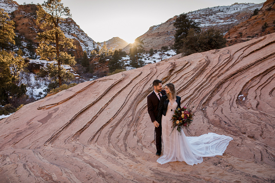 Utah-Shoot-bride-and-groom-standing-on-rock-cliff-bride-in-a-flowing-tulle-gown-and-lace-bodice-with-a-leather-jacket-while-the-groom-is-in-a-burgundy-tuxedo-with-a-long-black-tie