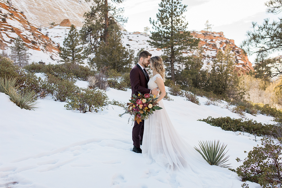 Utah-Shoot-bride-and-groom-touching-heads-bride-in-a-flowing-tulle-gown-and-lace-bodice-with-a-leather-jacket-while-the-groom-is-in-a-burgundy-tuxedo-with-a-long-black-tie