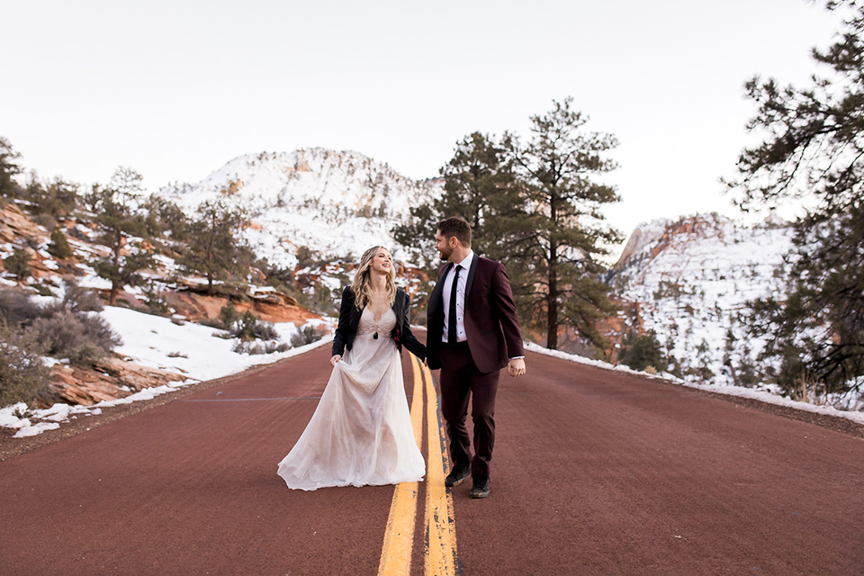 Utah-Shoot-bride-and-groom-walkking-on-the-road-bride-in-a-flowing-tulle-gown-and-lace-bodice-with-a-leather-jacket-while-the-groom-is-in-a-burgundy-tuxedo-with-a-long-black-tie