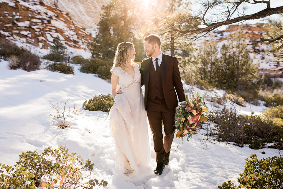 Utah-Shoot-couple-walking-in-snow-bride-in-a-flowing-tulle-gown-and-lace-bodice-with-a-leather-jacket-while-the-groom-is-in-a-burgundy-tuxedo-with-a-long-black-tie
