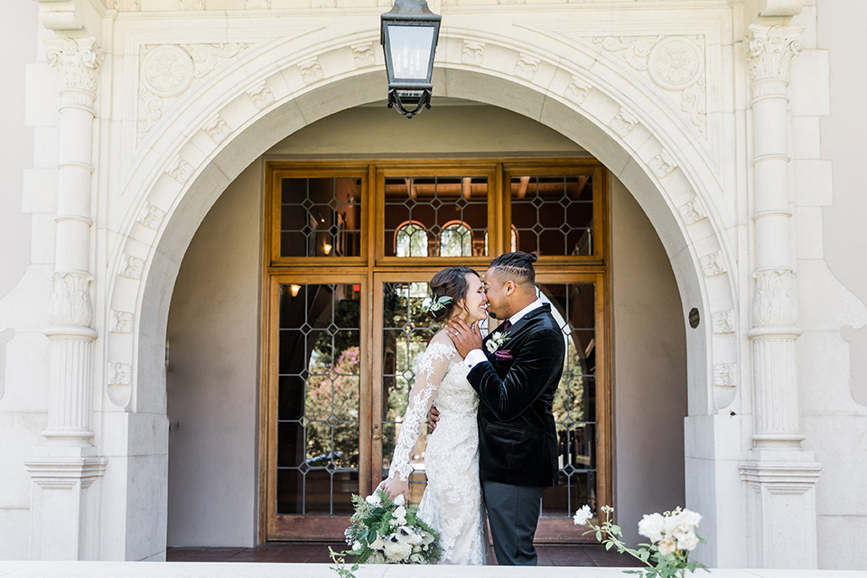 Maxwell-House-bride-and-groom-almost-in-front-of-the-venue-while-the-bride-is-wearing-a-lace-long-sleeved-gown-groom-in-a-black-velvet-tuxedo