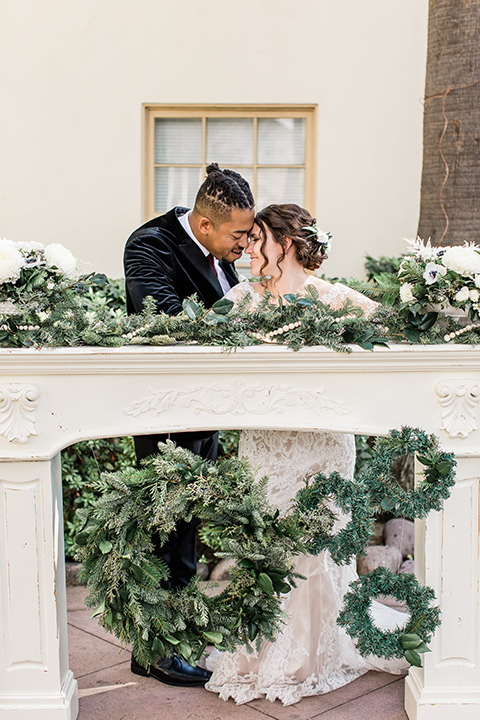 Maxwell-House-bride-and-groom-in-ceremony-space-bride-wearing-a-lace-long-sleeved-gown-groom-wearing-a-black-velvet-jacket