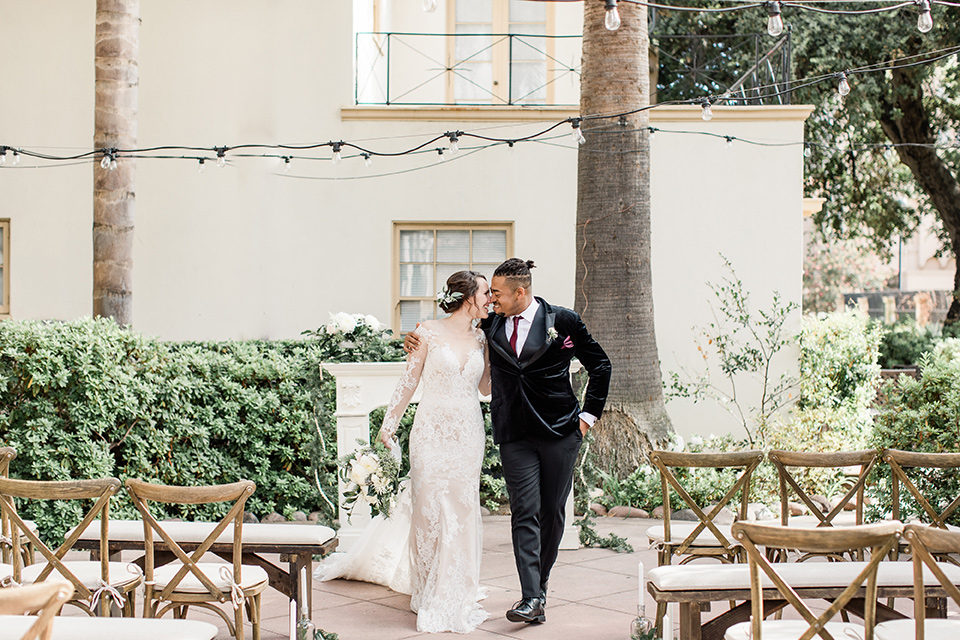 Maxwell-House-bride-and-groom-walking-away-from-ceremony-bride-is-wearing-a-lace-long-sleeved-gown-groom-in-a-black-velvet-tuxedo