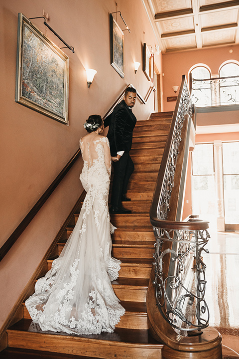 Maxwell-House-bride-and-groom-walking-up-the-stairs-bride-wearing-a-lace-long-sleeved-gown-groom-wearing-a-black-velvet-jacket
