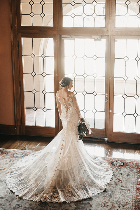 Maxwell-House-bride-by-the-windows-wearing-a-lace-gown-with-sleeves-with-a-deep-v-neckline